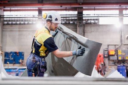 En medarbetare sätter skyddsfilt på den svängda trappan, tillverkad i Norberg.